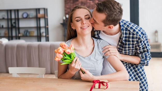 Man kissing happy wife and giving presents Free Photo