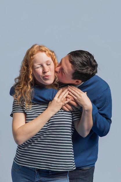 Man kissing his friend on the cheek Free Photo