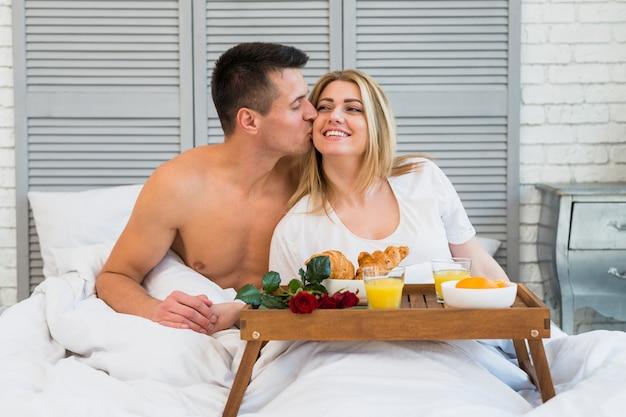 Man kissing smiling woman in bed near breakfast on board Free Photo