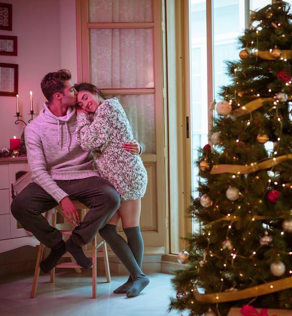 Man kissing woman on forehead near christmas tree Free Photo