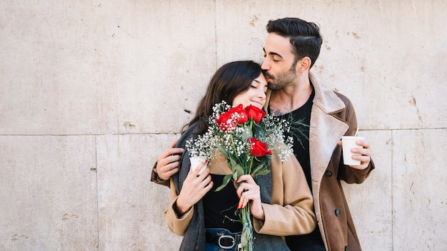 Man kissing woman with bouquet Free Photo