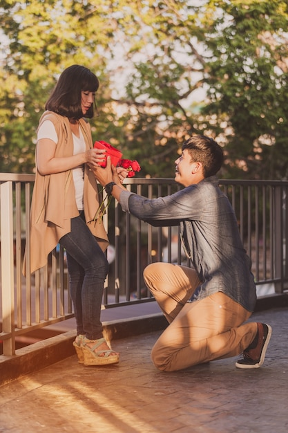 Man kneeling giving his girlfriend roses and a red gift Free Photo