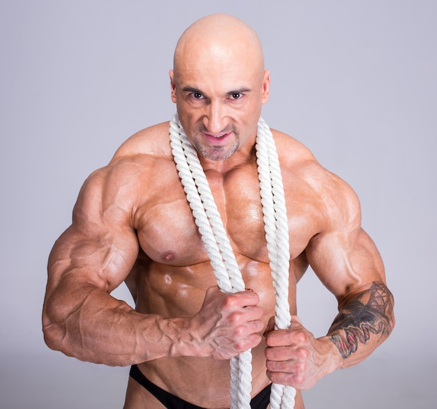 A man laid a rope on his neck and harnessed his muscles. Premium Photo