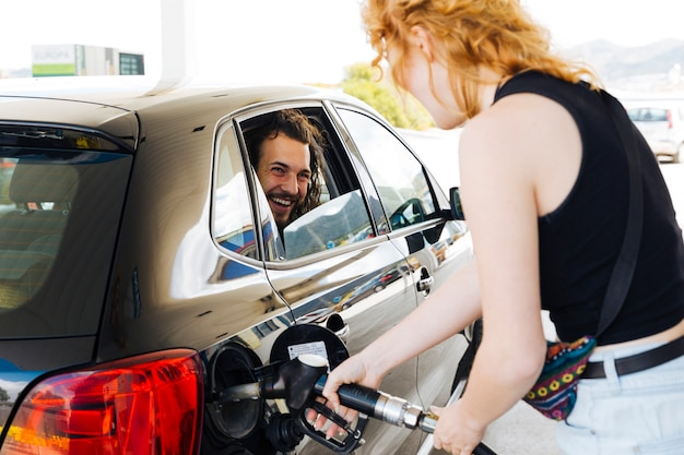Man laughing out of car window with woman filling up car Free Photo