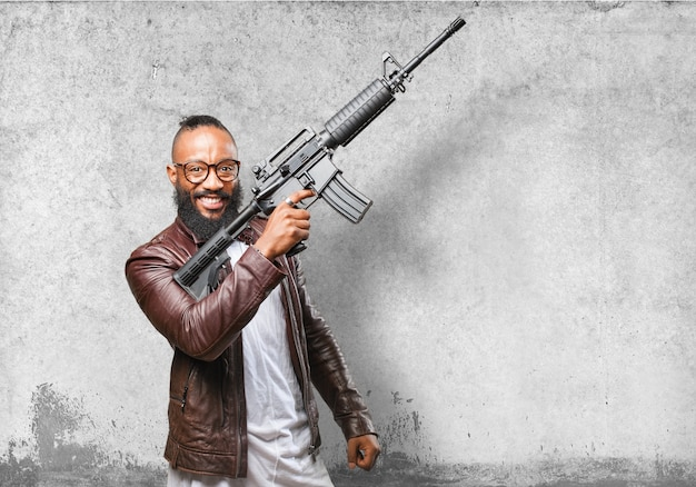 Man laughing while pointing a machine gun at the sky Free Photo