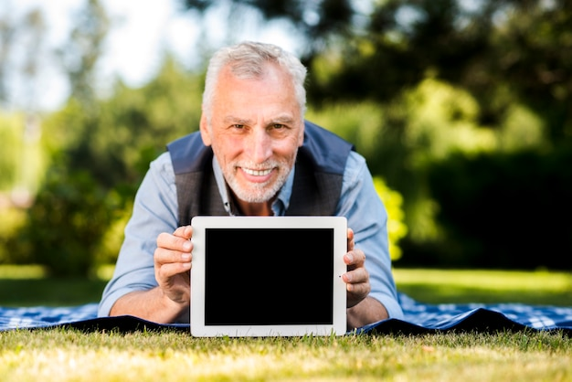 Man laying on a blanket with a tablet mockup Free Photo