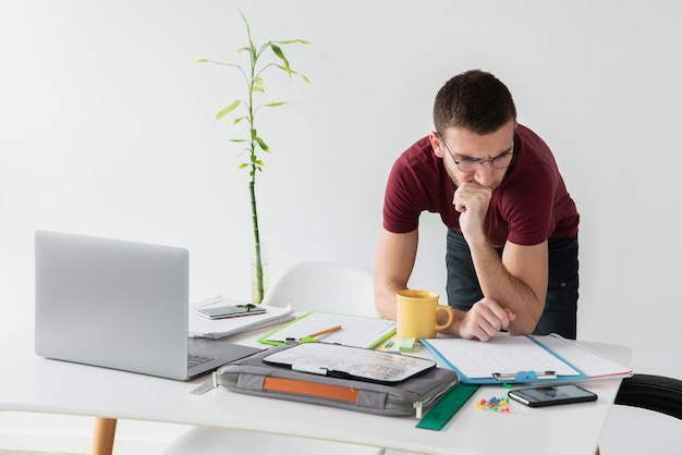 Man leaning on his desk and being focused Free Photo