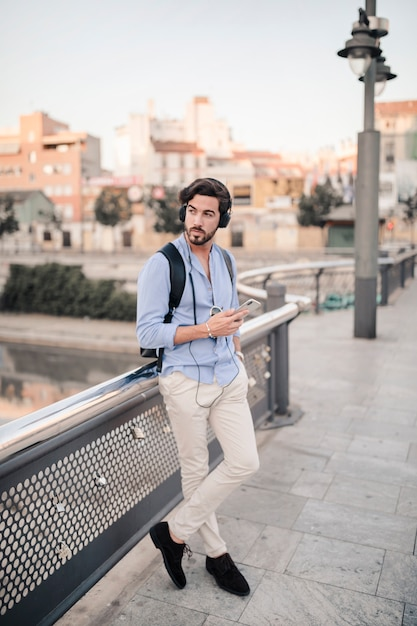 man leaning on railing listening to music photo free download