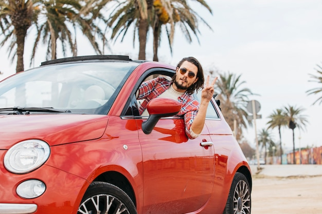 Man leaning out from car and showing peace gesture Free Photo