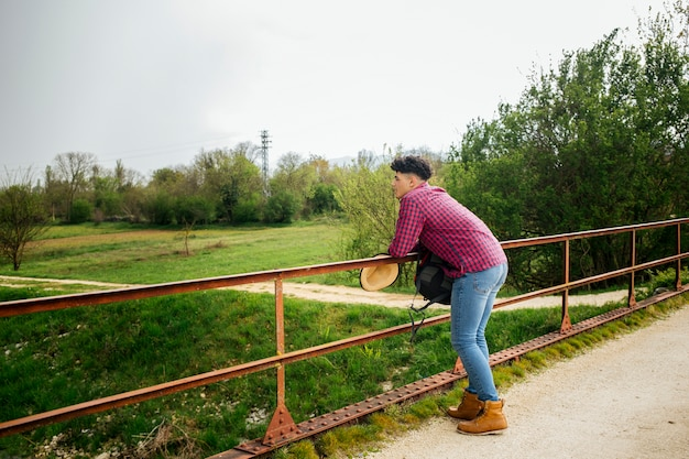 Man leaning on railing looking at nature Free Photo