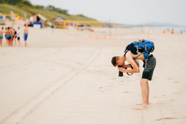 男は身を乗り出し、ビーチで砂の写真を撮ります。 Premium写真