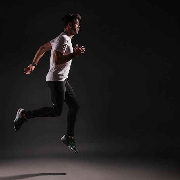 Man leaping on dark background Free Photo