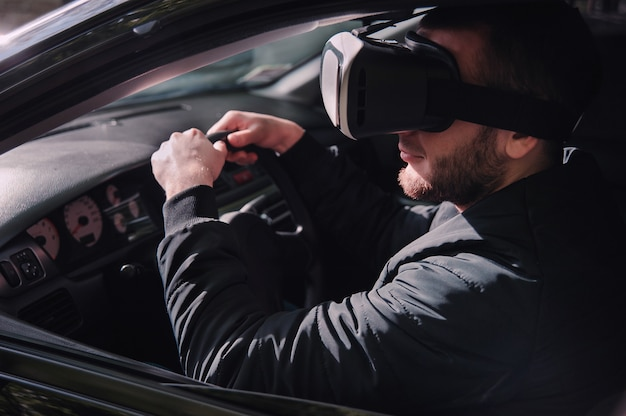 Man learning to drive with virtual reality glasses Premium Photo
