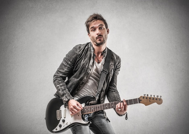 Man in leather jacket playing on a guitar Premium Photo