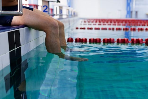 Gambe dell'uomo che entrano nell'acqua della piscina Foto Gratuite