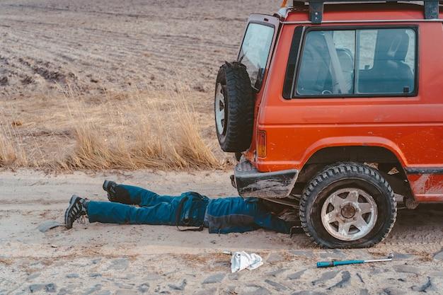 未舗装の道路で4x4車の下に横たわる男 無料写真