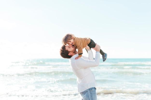 Man lifting baby boy up on seashore Free Photo