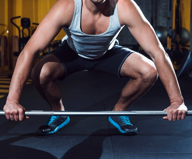 Man lifting barbell in fitness club Free Photo
