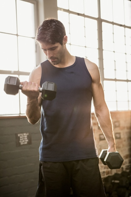 Man lifting dumbbell while looking down Premium Photo