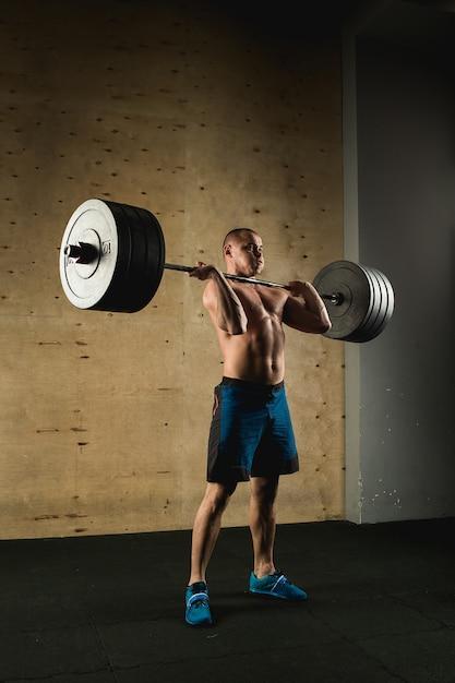 重りを持ち上げる男。バーベルの演習を行うジムで筋肉男のトレーニング Premium写真