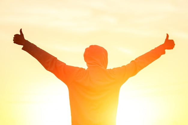 A man in the light of the sunset with his hands up Premium Photo