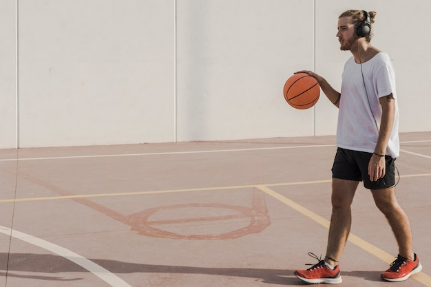 Man listening to music on headphone walking with basketball in court Free Photo