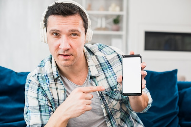 Man listening music in headphones and pointing at smartphone on settee Free Photo