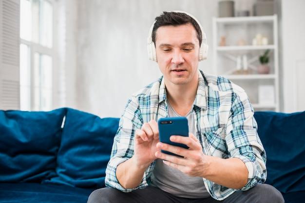 Man listening music in headphones and using smartphone on sofa Free Photo