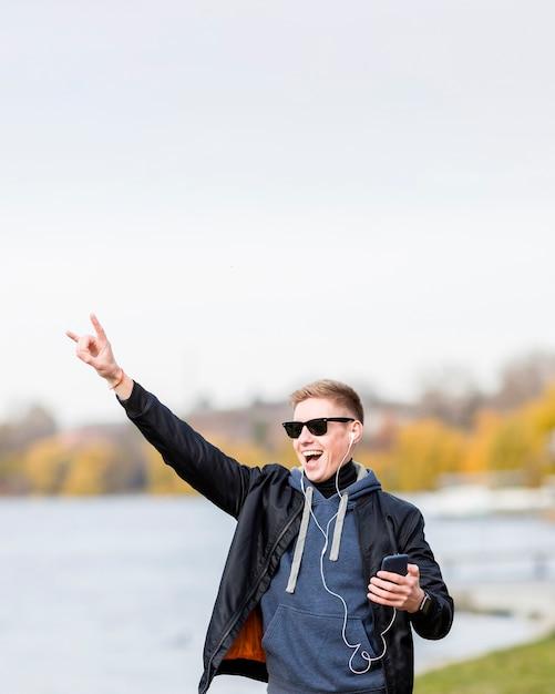 コピースペースで屋外のイヤホンで音楽を聞いている男性 無料写真