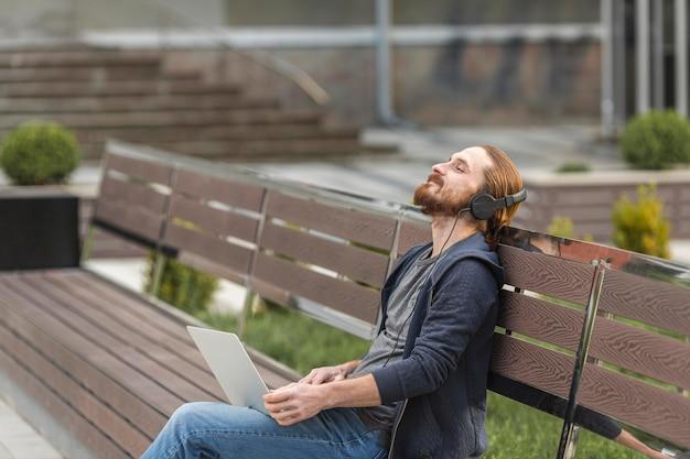 市内の屋外のヘッドフォンで音楽を聞いている男性 無料写真