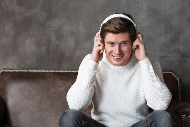 座っている間ヘッドフォンで音楽を聞いている男性 無料写真