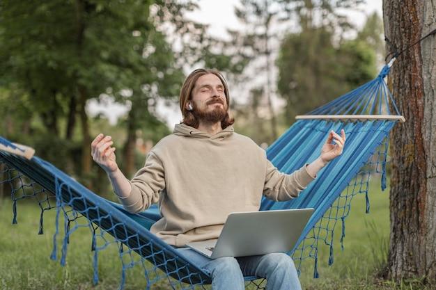 ハンモックに座りながら禅の音楽を聞いている男性 無料写真