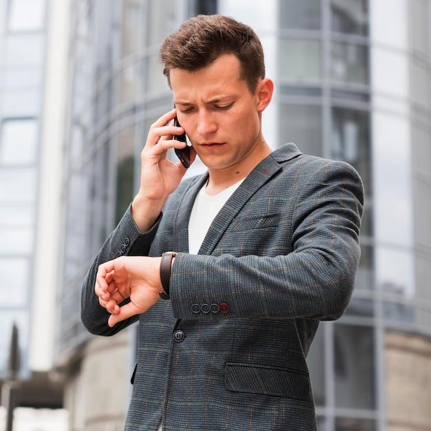 Человек смотрит на часы и разговаривает по телефону по дороге на работу Бесплатные Фотографии