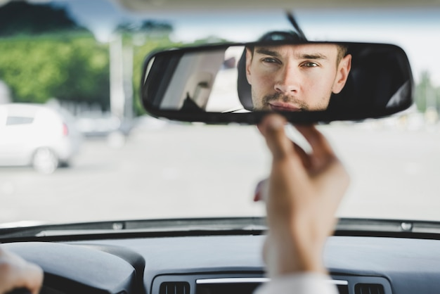 Man looking back through the rear view mirror from the front seat of a car Free Photo