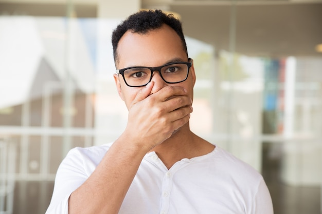 Man looking at camera, closing mouth with hand, looking shocked Free Photo