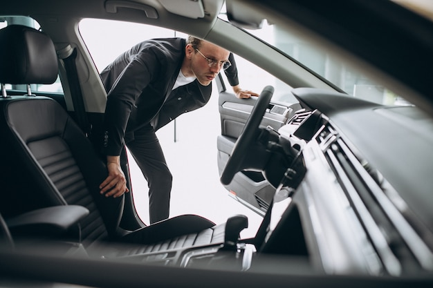 Man looking at a car in a car showroom Free Photo