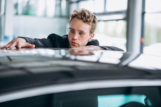 Man looking at a car and thinking of a purchase Free Photo