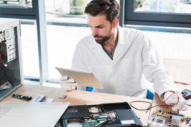 Man looking at digital tablet while repairing computer in workshop Free Photo