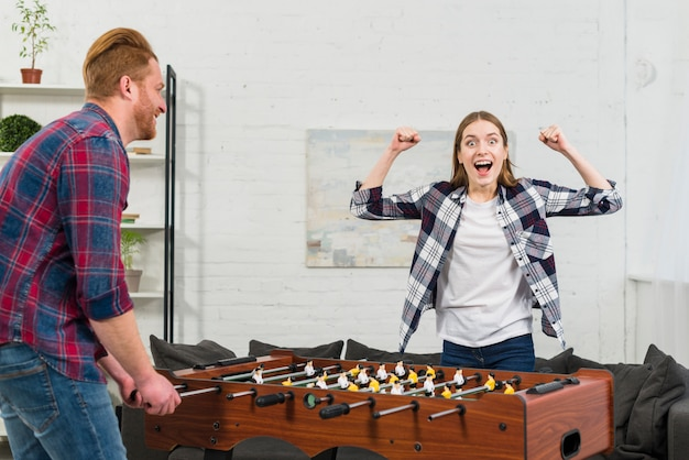Man looking at her girlfriend cheering after winning the table soccer Free Photo