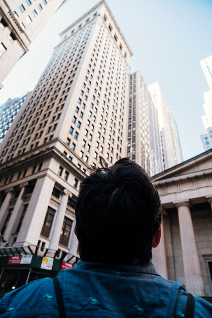 Man looking at high skyscrapers Free Photo