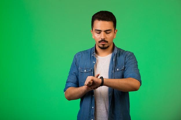 Uomo che guarda l'orologio, controlla l'ora in modo tranquillo. Foto Gratuite