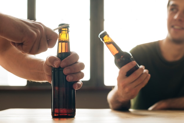 A man looking at a person opening brown beer bottle in restaurant Free Photo