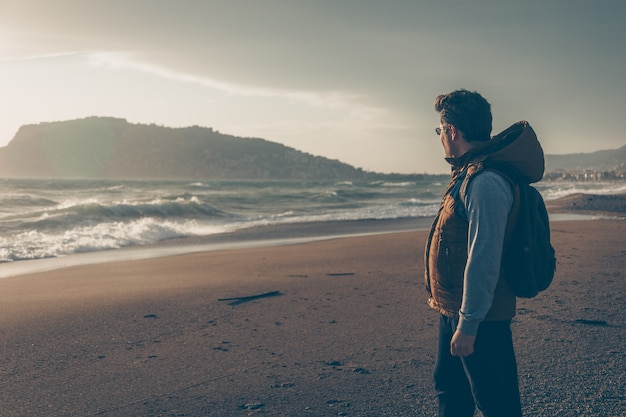 Man looking at sein beach during daytime and looking thoughtful Free Photo