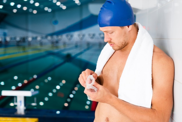 Man looking at swimming goggles Free Photo