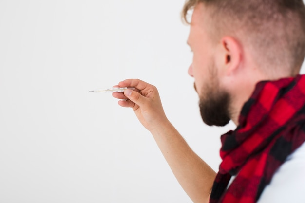 Man looking at thermometer Free Photo
