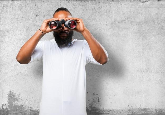 Man Looking Through Binoculars With Gray Background Photo