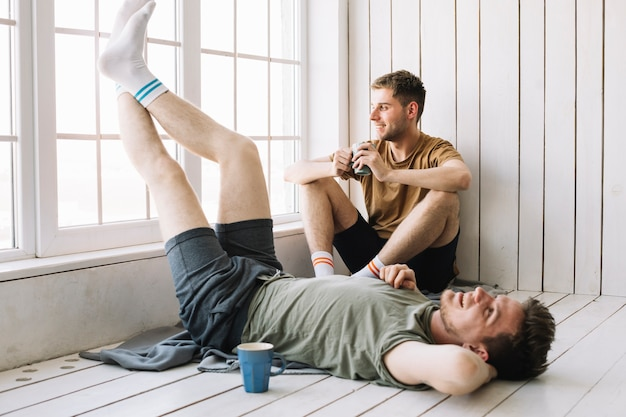 Man looking through window while his friend lying on floor Free Photo