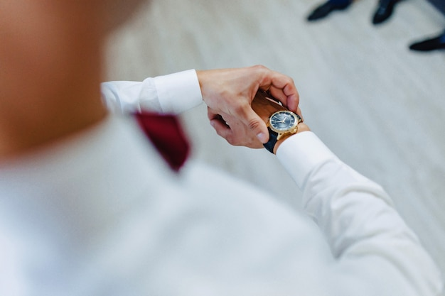 Man looking at the time on his wrist watch Free Photo