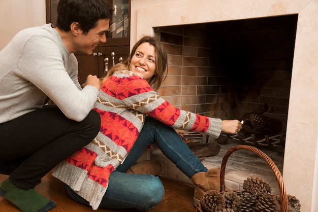 Man looking at young woman ignite big match in the fireplace Free Photo