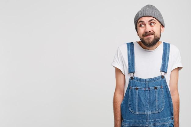 男は空白のコピースペースを脇に見て、罪悪感のある謝罪の表現で立っています 無料写真